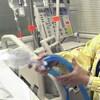 Une infirmière tient dans ses mains des tubes attachés à un respirateur artificiel.