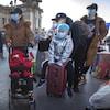 Des voyageurs portent un masque pour se déplacer dans les espaces publics.