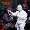 Une journaliste de l'agence Reuters ouvre la bouche pour subir un test de dépistage pour la COVID-19 à Wuhan, en Chine.