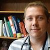 Le Dr Cory Scott pose pour la caméra dans un bureau de médecin.