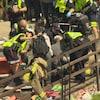 Sur la photo on voit des policiers et des pompiers secourir une victime