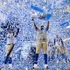Des joueurs de football célèbrent leur victoire au milieu de confettis.