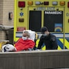 Un homme âgé dans une civière descend d'une ambulance avec l'aide de deux paramédics.