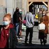 Scène sur un trottoir. Les passants portent le masque.