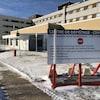 Un petit bâtiment couvert où peut pénétrer une voiture adjacent à un hôpital.