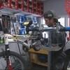 Un homme répare un vélo dans un atelier.