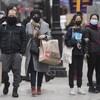 Des gens portant des masques marchent au centre-ville.