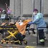 Deux ambulanciers poussent une civière sur laquelle est couchée une résidente du foyer Rockcliffe.