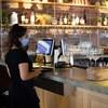 Deux serveurs portent un masque dans le bar où ils travaillent.