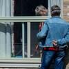 Deux personnes sont séparées par une fenêtre