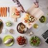 Un homme a coupé en dé des courgettes, des tomates,des betteraves jaunes. Il verse les morceaux dans un bol.