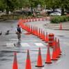 Un cycliste sur une voie réservée entourée de cônes orange.