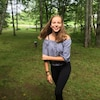 Lexi Daken, souriante, dans un parc.