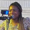 Une jeune femme avec de longs cheveux tressés, vêtue d'une robe fleurie, souriante, devant un micro, sur une scène.