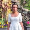 Une photo de Danielle Parent, une femme aux cheveux attachés derrière sa tête portant des boucles d'oreille blanches et une robe blanche.