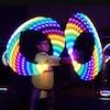 Thelan-Kicknosway, en habits traditionnels autochtones, fait tourner sur son bras 2 cerceaux illuminés aux couleurs de l'arc-en-ciel.