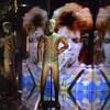 Un mannequin porte un costume bariolé devant un écran montrant David Bowie qui chante.