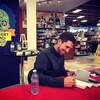 David Goudreault qui signe un livre devant une grande affiche de son livre.