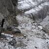 Paysage de montagne rocheuse avec des bâtons de marche en avant-plan.