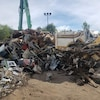 Une pile de déchets métalliques entassés à l'extérieur avec en arrière-plan des arbres aux feuilles vertes et un ciel bleu.