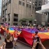 Des gens marchent en tenant un bout du drapeau arc-en-ciel.
