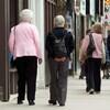 Des gens âgés marchent sur un trottoir.
