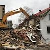Une pelle mécanique détruit la maison.