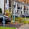 Des balises de déneigeurs plantées sur des terrains de clients, à côté de voitures stationnées.