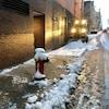 Un petit tracteur pousse la neige en bas du trottoir.
