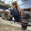 Plan large, d'une jeune femme manipulant un moteur.