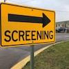 Une pancarte jaune sur laquelle le mot SCREENING est écrit, avec une flèche pointant vers un bâtiment.