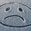 Le blues de l'hiver représenté par le dessin d'un visage triste dessiné dans la neige.