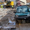 Une voiture endommagée sur une route défoncée avec des travailleurs et une excavatrice à l'arrière-plan.