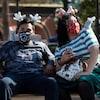 Un couple masqué portant des accessoires de Disney sont assis sur un banc public.