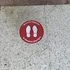 Un collant sur le sol près d'un commerce indique : « Merci de respecter la distance physique ».