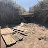 Planches brisées d'un trottoir en bois et sable d'une plage.