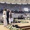 Melania et Donald Trump suivent Narendra Modi sur une scène.