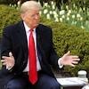 Donald Trump, assis sur un banc, s'adresse à un journaliste vu de dos.