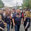 Doug Ford marche dans la foule dans la rue avec un tshirt aux couleurs LGBTQ+.