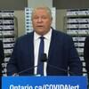Le premier ministre est au podium lors d'une conférence de presse, les ministres sont éloignées et portent des masques médicaux.