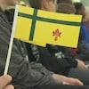 Un jeune tient un petit drapeau fransaskois dans les mains.