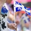 Une femme habillée de noir, blanc et bleu tient un drapeau du Québec.