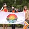 Trois personnes tiennent un drapeau wolastoqey.