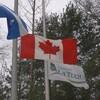 Les drapeaux du Québec, du Canada et de La Tuque, en berne.