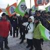 Des chauffeurs bien habillés pour l'hiver brandissent leurs drapeaux de la CSN.