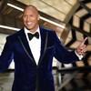 Dwayne Johnson porte un costume en velours bleu et il pointe les doigts vers le ciel.
