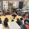 Des élèves de 2e-3e année de l'école francophone de l'Anse-au-sable de Kelowna, assis en cercle sur le plancher de la classe, participent à une activité en français.