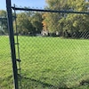 Un terrain vert qu'on voit au travers d'une clôture.
