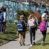 Des élèves avec des sacs à dos marchent dehors.
