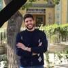 Amir Hossein Saeedinia pose, souriant, devant une maison, en été.